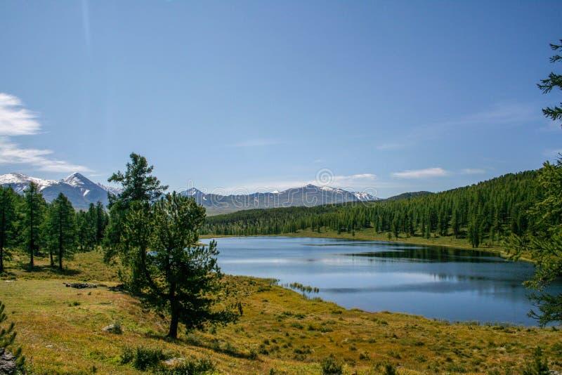 Bel horizontal de montagne Montagnes couronnées de neige, lac image stock