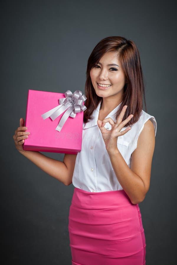 Bel OK asiatique d'exposition de fille avec un boîte-cadeau photos libres de droits