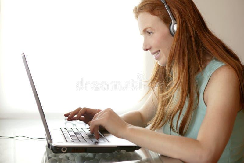 Bel ordinateur portatif roux d'étudiant de secrétaire photographie stock