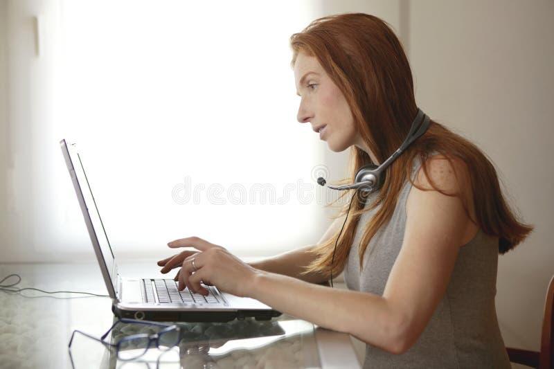 Bel ordinateur portatif roux d'étudiant de secrétaire image stock