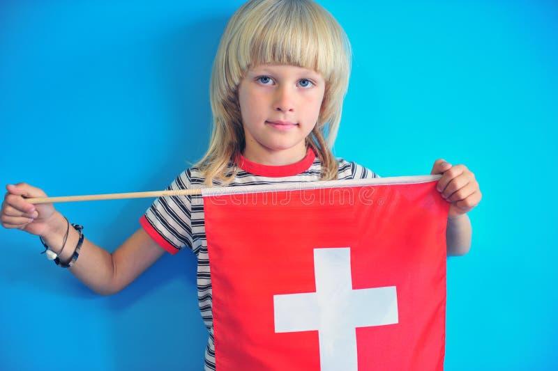 Bel ragazzo che tiene bandiera nazionale della Svizzera immagini stock