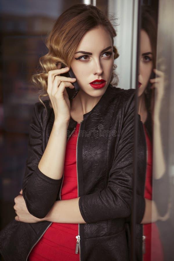 Bela morena sexy-agente de espionagem assassinadora ou policial na jaqueta de couro e vestido vermelho de luxo com um binocular n imagens de stock