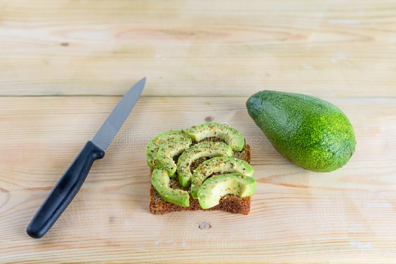 Belamente pão do brinde do centeio com o abacate verde cortado imagens de stock royalty free
