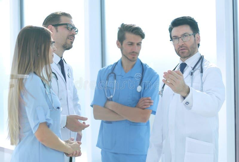 Belangrijke arts die met het ziekenhuispersoneel spreken royalty-vrije stock afbeelding