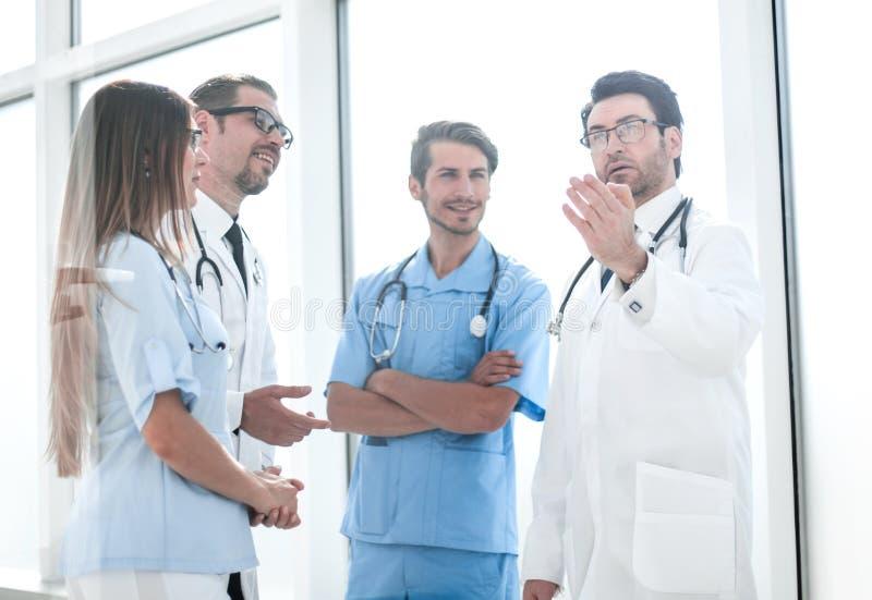 Belangrijke arts die met het ziekenhuispersoneel spreken royalty-vrije stock afbeeldingen