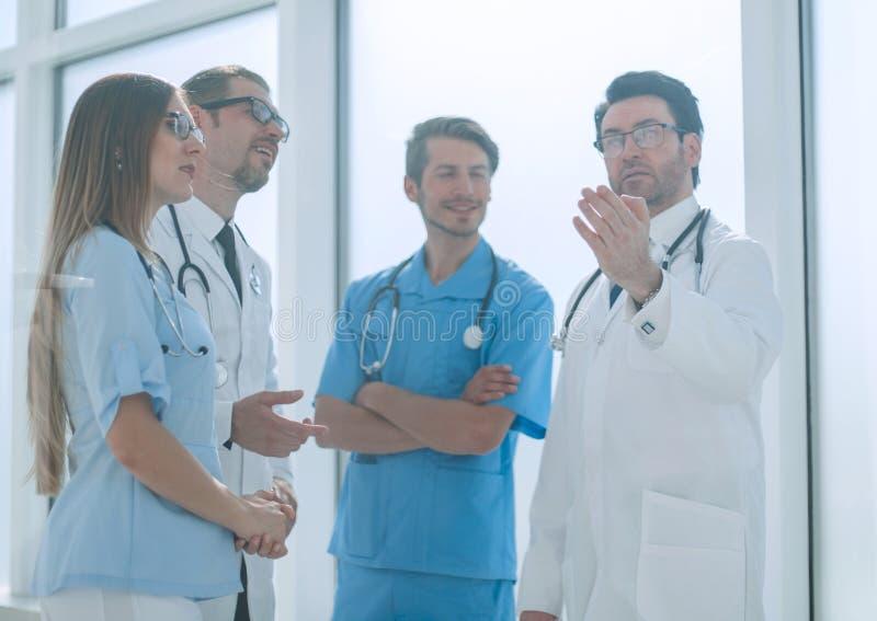 Belangrijke arts die met het ziekenhuispersoneel spreken stock afbeeldingen