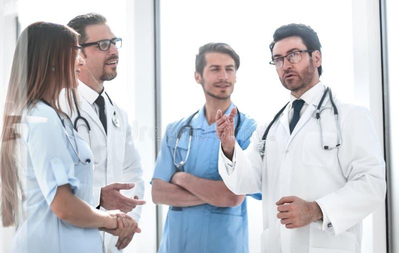 Belangrijke arts die met het ziekenhuispersoneel spreken royalty-vrije stock foto's