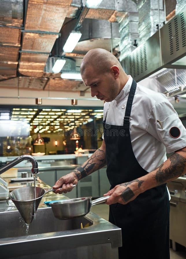 Belangrijke Stap Het verticale portret van knappe professionele chef-kok in schortholding kookte deegwaren in een vergiet onder w stock foto's
