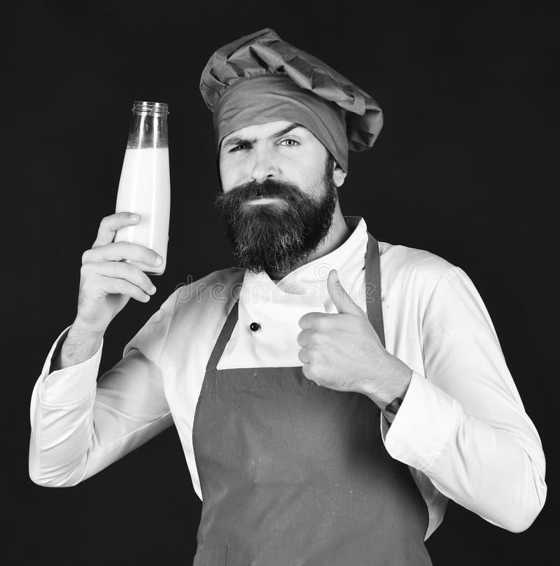 Belangrijkste kooktoestel of chef-kok Chef-kok met milkshake of yoghurt Kok met zeker gezicht stock afbeelding