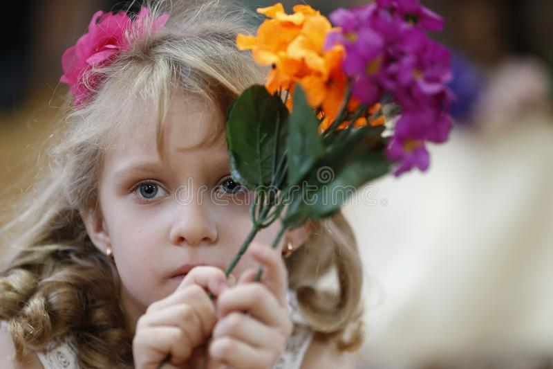 Girl with artificial flowers royalty free stock photography