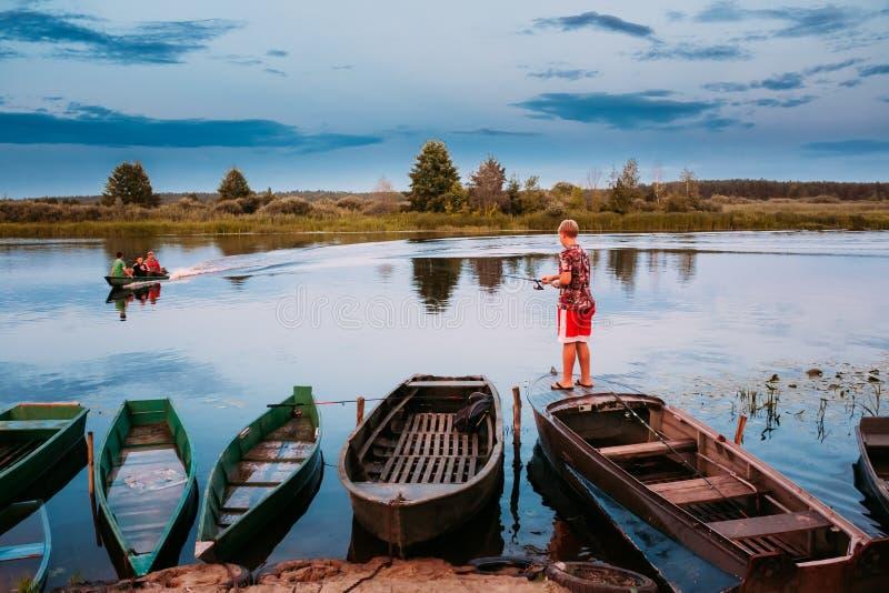belarus Enfants biélorusses pêchant de vieux bateaux de rangée en bois pendant l'été image libre de droits