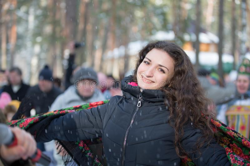 Belarus, Gomel, February 18, 2018. Russian holiday seeing off winter Maslenitsa.Beautiful brown-eyed brunette in Russian scarf in stock image