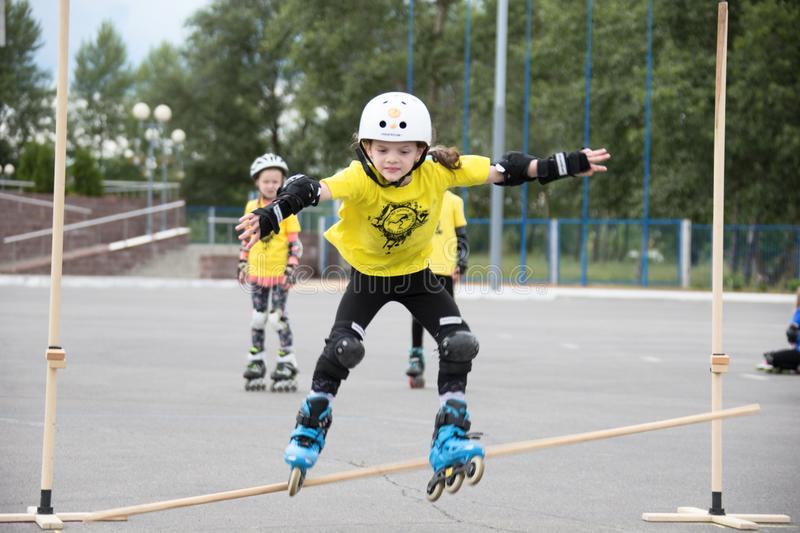 Children`s competition in roller sport.The girl jumps on rollers through a barbell stock photos