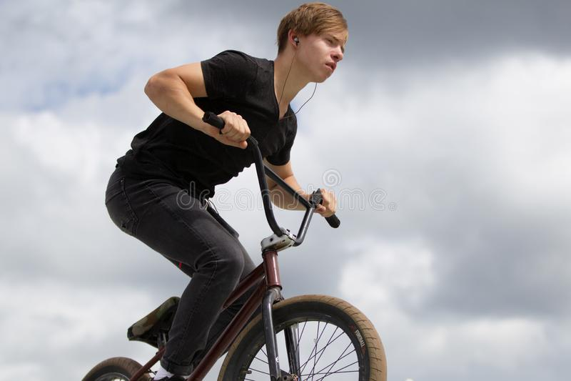 Cyclist on the sky.A guy on a bicycle is riding against the sky stock photography
