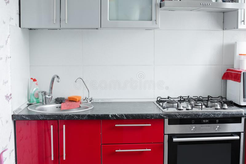 Belarus Minsk 06 12 2019Beautiful modern clean red kitchen in small apartment full shot royalty free stock images