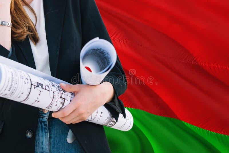 Belarusian architekta kobiety mienia projekt przeciw Białoruś falowania flagi tłu Budowy i architektury poj?cie zdjęcia stock