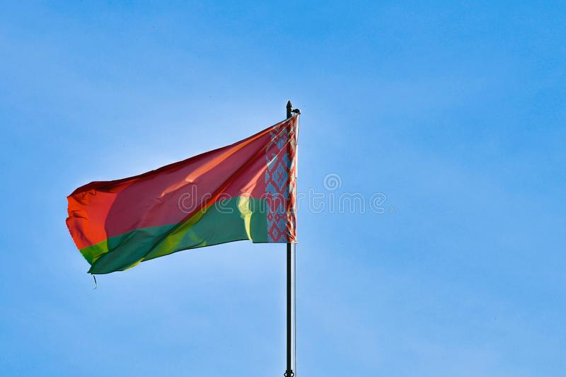 Belarusian flag on sky background. Develops in the wind. Flag of Belarus stock photo