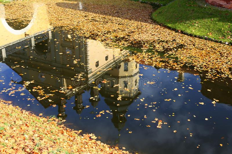 Belarusian tourist landmark attraction Nesvizh Castle - medieval castle in Nesvizh, Belarus reflection in water with yellow leaves.  stock photos
