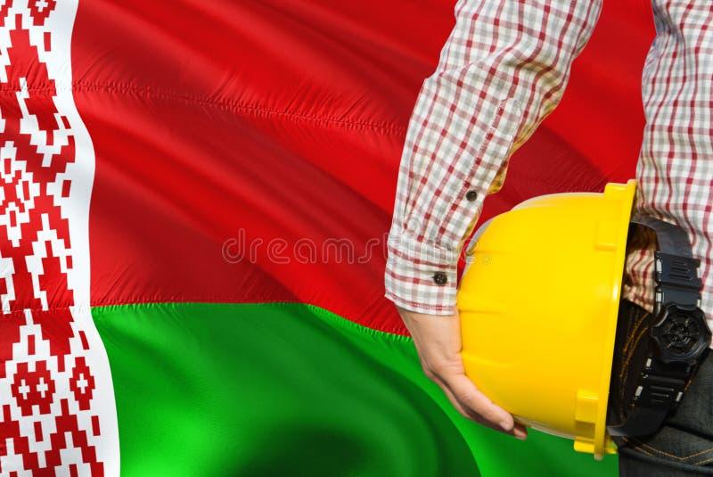 Belarussischer Ingenieur hält gelben Schutzhelm mit dem Wellenartig bewegen des Weißrussland-Flaggenhintergrundes Bau- und Geb?ud stockbild