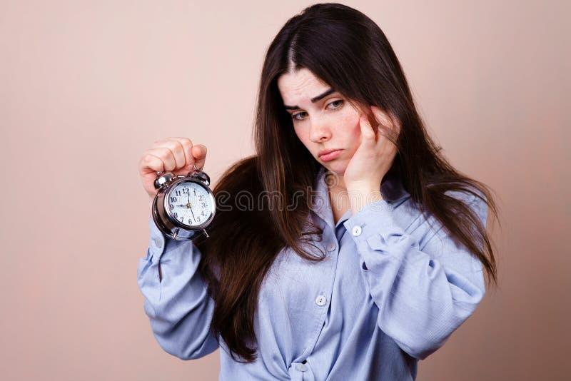 belastad affärskvinna med ringklockan, stopptid arkivfoto