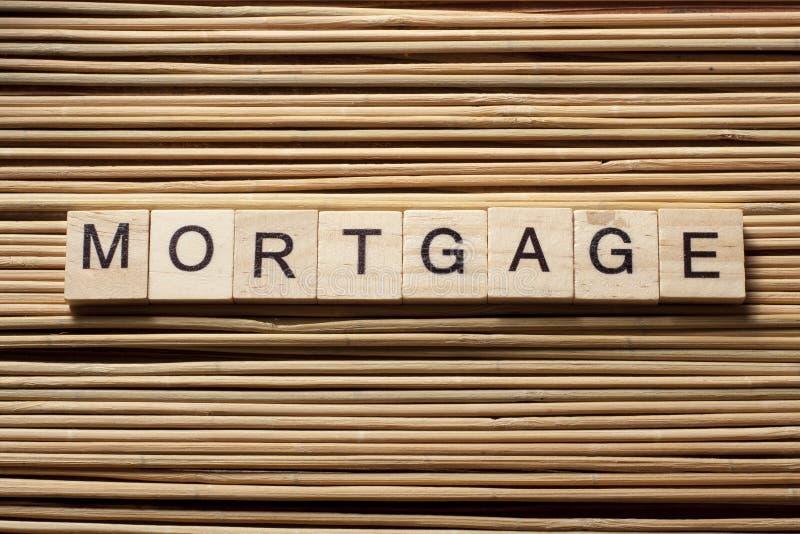 BELASTEN Sie das Wort hypothekarisch, das auf hölzernen Block am hölzernen Hintergrund geschrieben wird stockbild