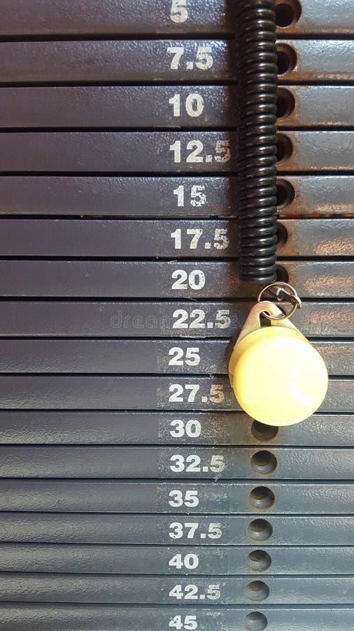 Belasten Sie Stapelgraustufen mit Staffelung in den Kilogramm mit gelbem Stift lizenzfreie stockfotos