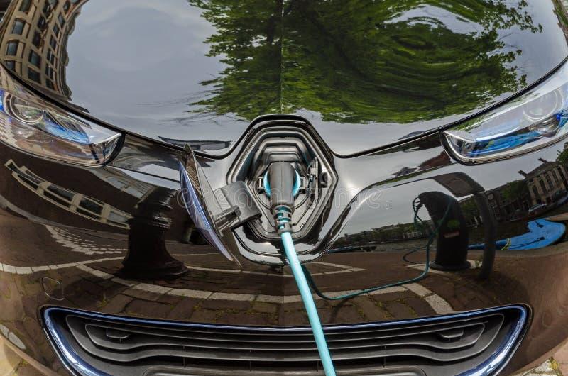 Belastend moderne elektrische die auto met voeding wordt gestopt in stock fotografie