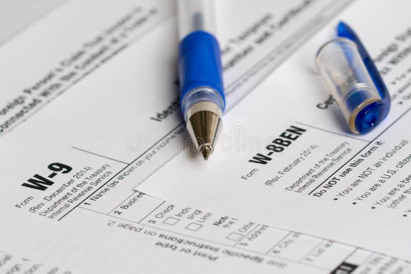 Belasting rapporteringsvormen met geopende blauwe pen stock afbeeldingen