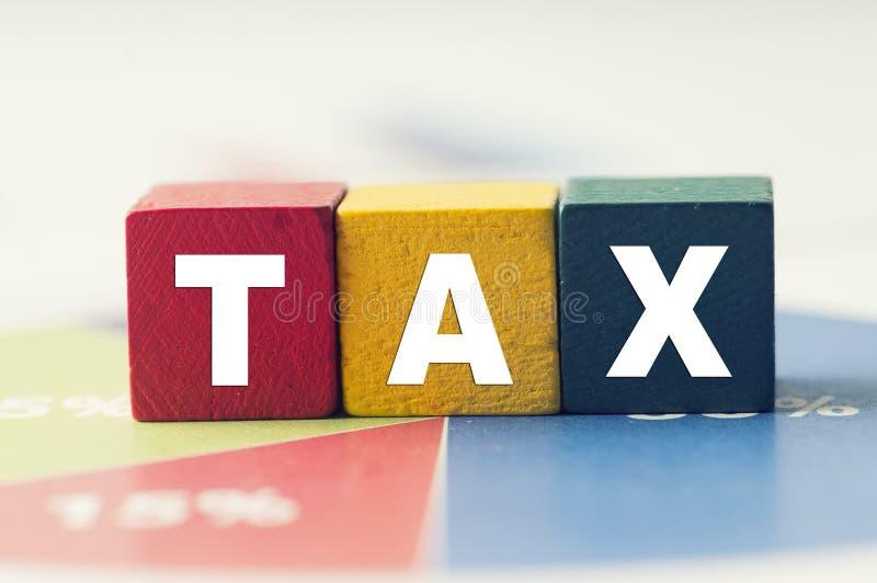 Belastingconcept met kleurrijk houten belastingwoord op cirkeldiagram royalty-vrije stock afbeeldingen