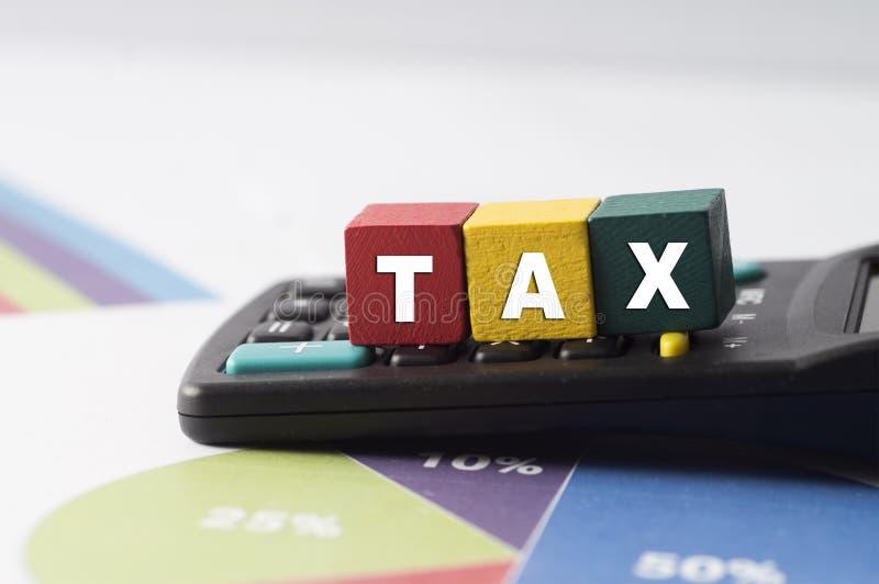 Belastingconcept met kleurrijk houten blok belastingwoord op rekenmachine royalty-vrije stock foto