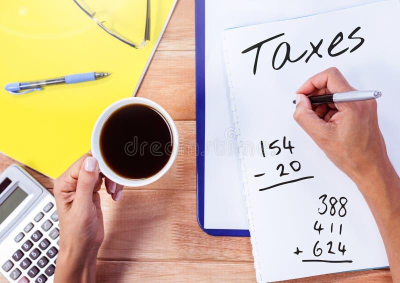 Belastingentekst op pagina met koffie en calculator wordt geschreven die royalty-vrije stock afbeelding