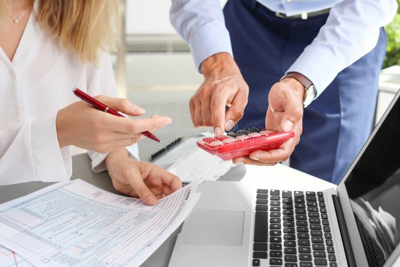 Belastingsaccountants die met documenten werken stock foto's