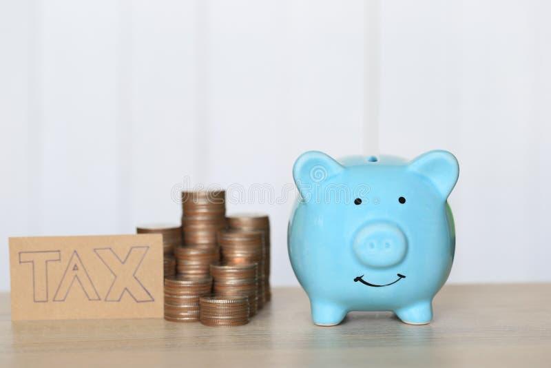 Belastingsconcept, Blauw spaarvarken met stapel van muntstukkengeld op witte achtergrond royalty-vrije stock afbeeldingen