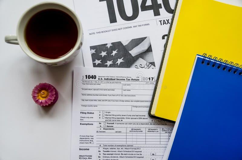 Belastingsvorm 1040, twee notitieboekjes en een kop thee op een witte achtergrond, een aromatische kaars royalty-vrije stock afbeeldingen