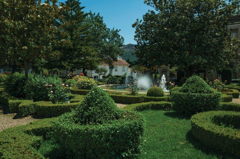 Belaubte Hecke und Büsche in einem hölzernen Garten mit Brunnen stockbilder