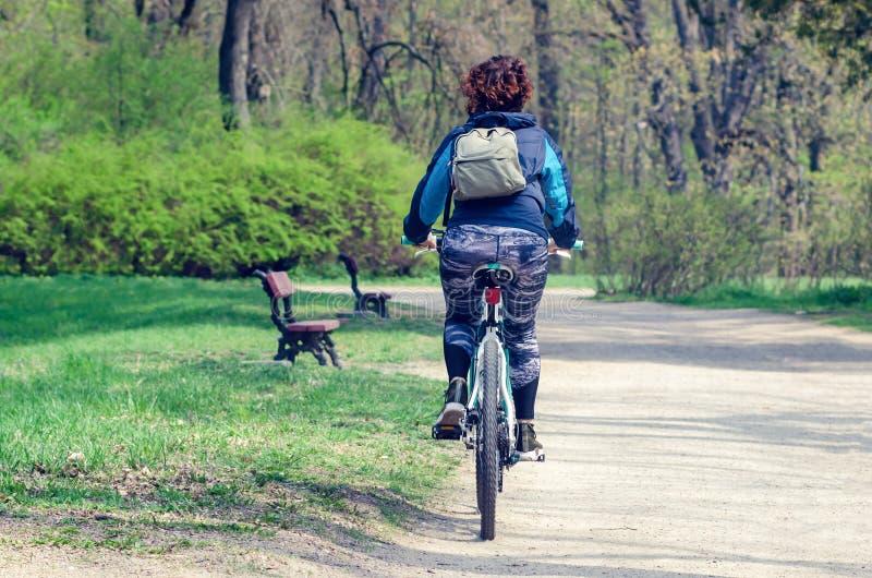 Belaya Tserkov, Ukraina, April 21, 2019: Flickan som rider en cykel i en stad, parkerar fotografering för bildbyråer