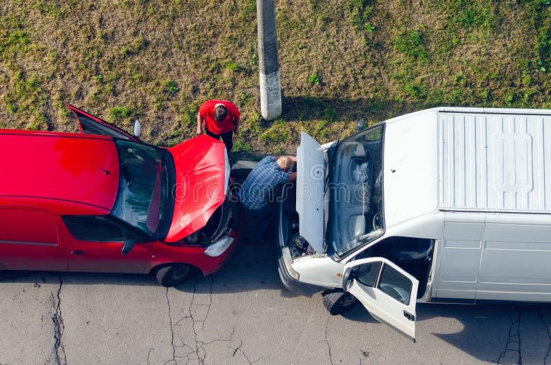 Belaya Tserkov, Ukraina - Maj 25, 2019: Bästa sikt, två män som reparerar bilar med lyftta huvar som står på sidan av vägen royaltyfri bild