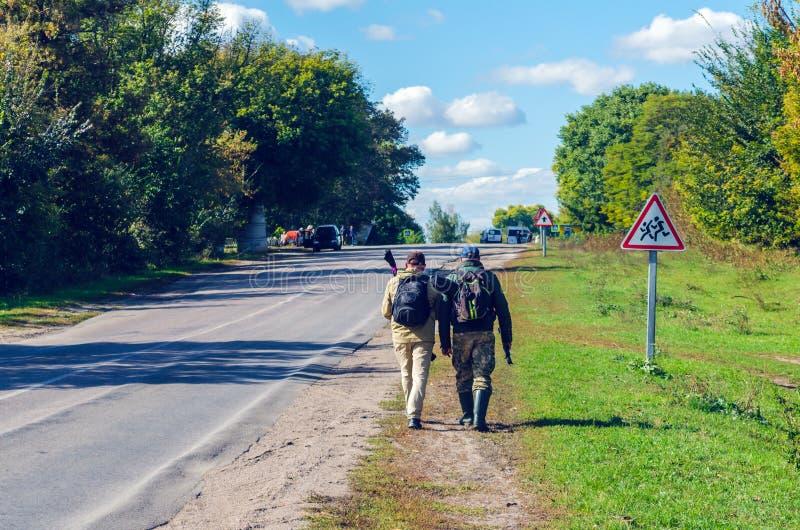 Belaya Tserkov, Ukraine, le 30 septembre 2018 : Deux hommes avec des sacs à dos marchent le long du côté de la route photos stock