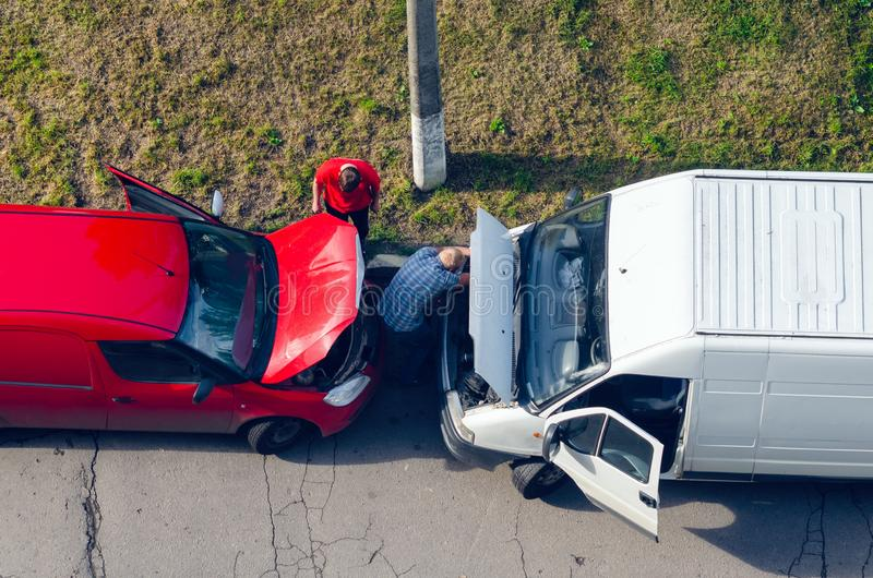 Belaya Tserkov, Ukraine - May 25, 2019: Top view, two men repairing cars with raised hoods standing on the side of the road. royalty free stock image