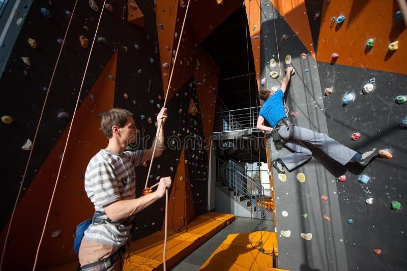 Belayer assicurando lo scalatore sulla parete della roccia all'interno immagine stock libera da diritti