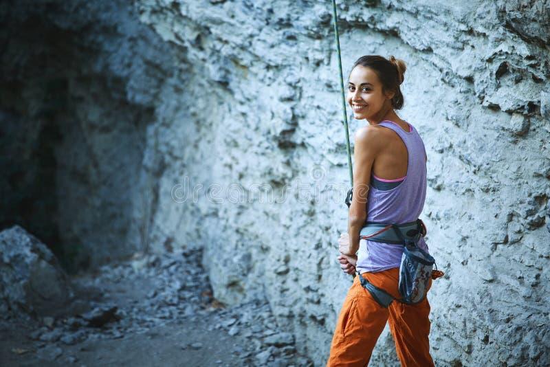 Belayer sorridente dello scalatore della donna con la corda immagine stock