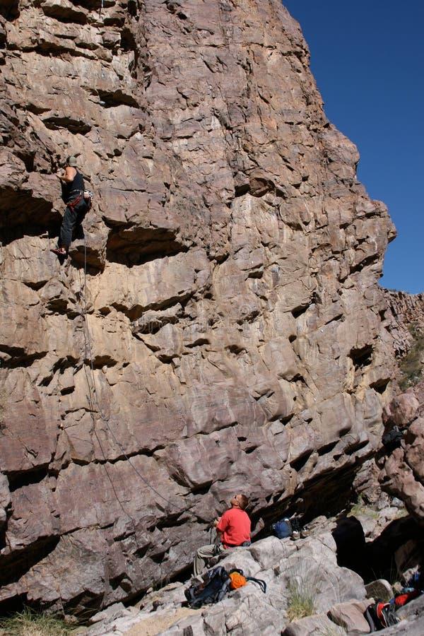 Belayer sotto lo scalatore sulla parete fotografie stock