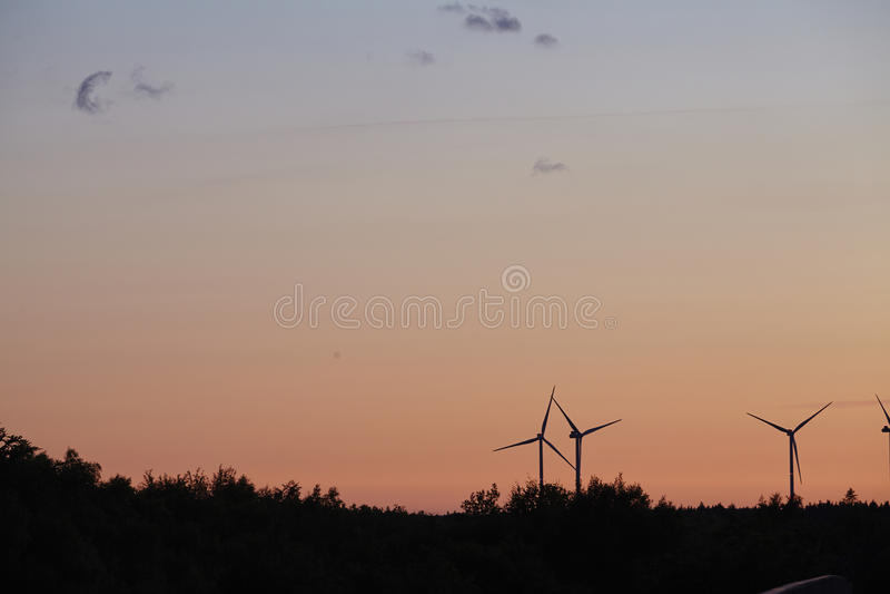 Beldorf - σταθμοί αιολικής ενέργειας στον ορίζοντα στο ηλιοβασίλεμα στοκ φωτογραφία