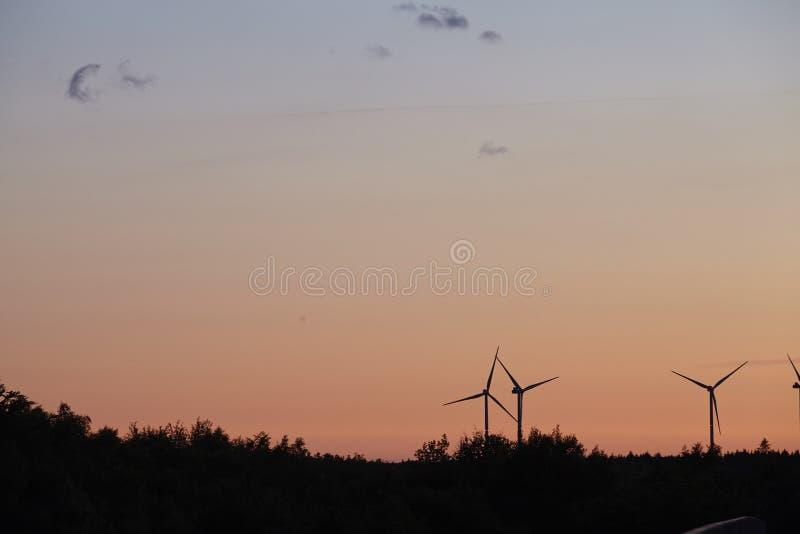 Beldorf - Windenergieposten bij de horizon op zonsondergang stock fotografie