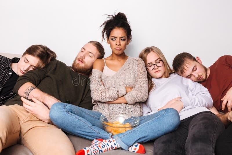 Beledigde damezitting op bank met chips en droevig het kijken opzij terwijl haar vrienden die dichtbij slapen royalty-vrije stock foto