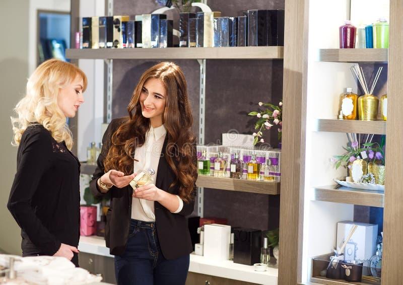 Beleefde vrouwelijke adviseur die klant met keus in schoonheidsmiddelenopslag helpen royalty-vrije stock fotografie