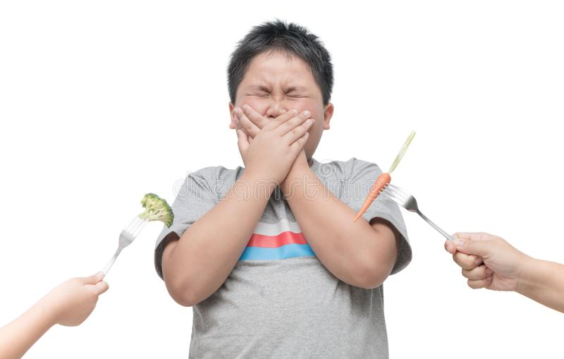 Beleibter fetter Junge mit Ausdruck des Ekels gegen Gemüse lizenzfreie stockbilder
