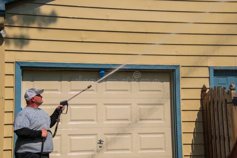 Beleibter kaukasischer Mann ist der Spritzdruck, der das Abstellgleis auf seinem Haus wäscht Der geschlossene Garagentor ist sich lizenzfreies stockbild