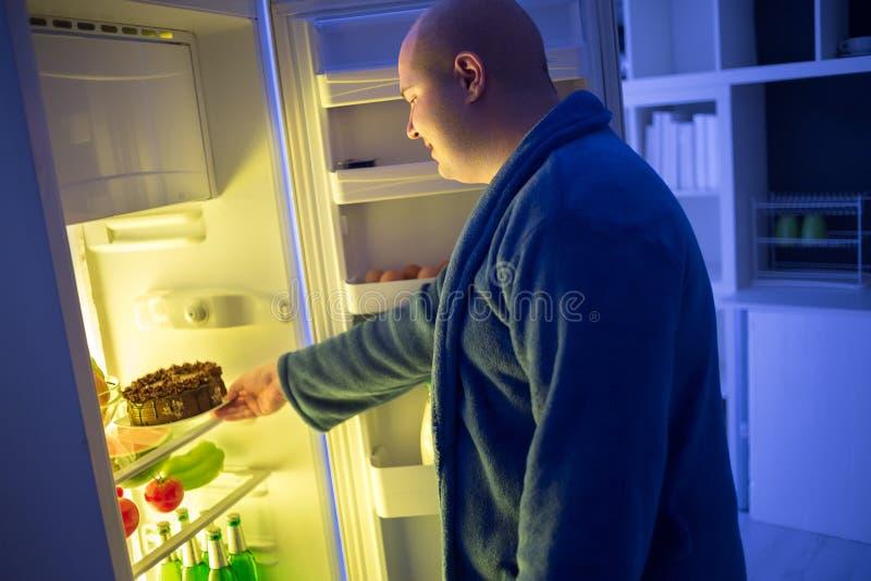 Beleibter Kerl am Nachtnehmen-Schokoladenkuchen lizenzfreies stockbild