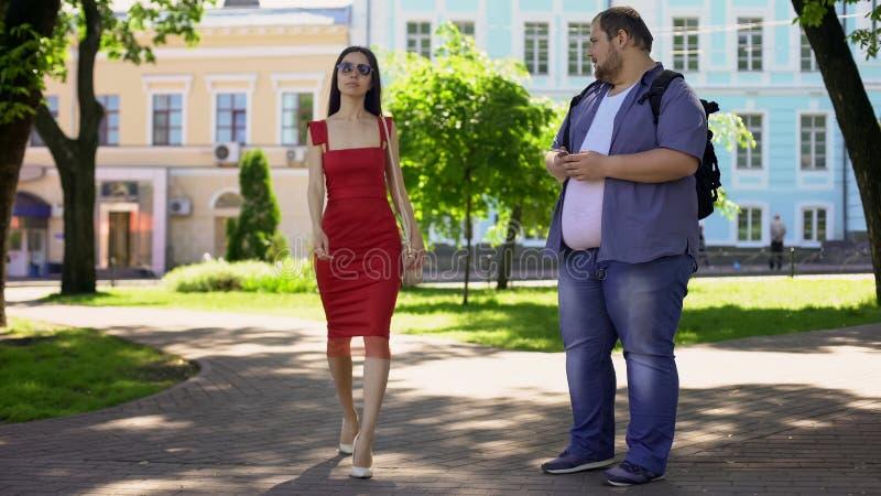 Beleibter Mann, der traurig recht dünne Dame im Kleid, Auftrittunsicherheit betrachtet stockfotografie